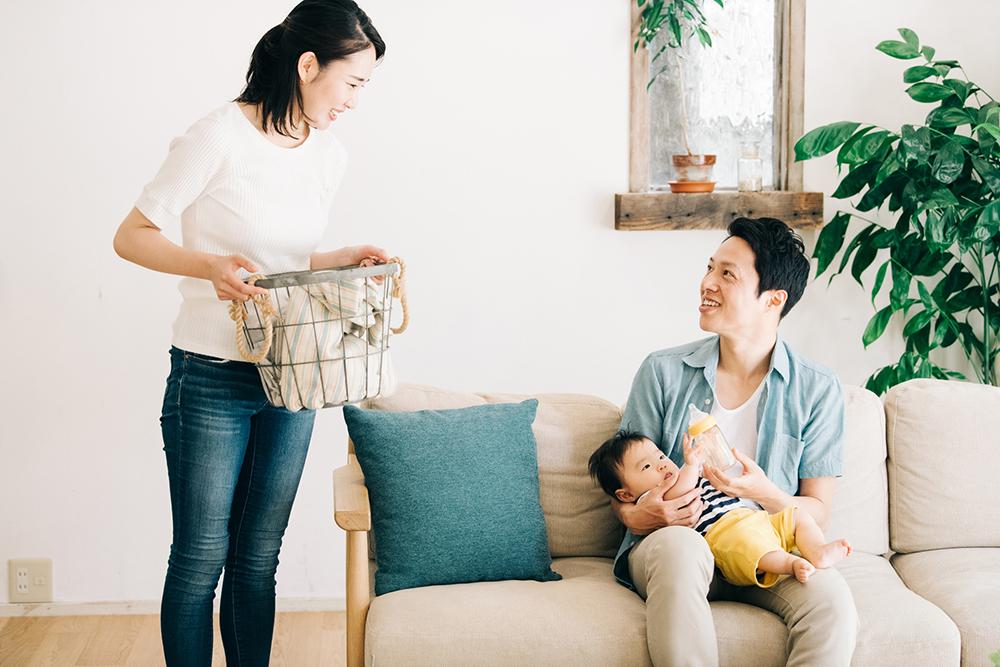赤ちゃんを抱く夫と洗濯をする妻