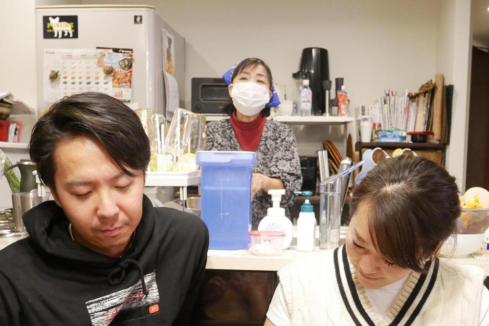 池田ご夫妻の後ろのキッチンに立つ黒田ママ